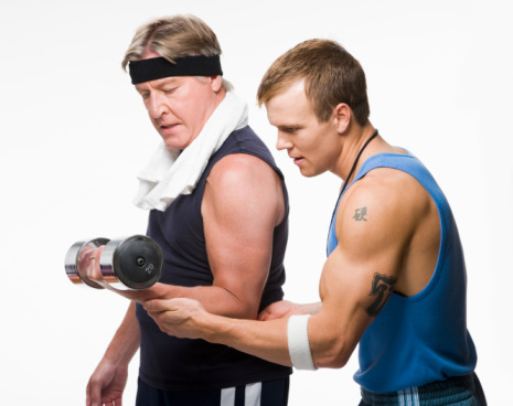 Fitness trainer helping mature man during exercising with weights