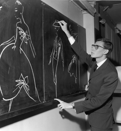 French designer Yves Saint-Laurent uses chalk to sketch fashion designs on a chalkboard in the atelier of the House of Christian Dior, where he had just been named as successor to couturier Christian Dior, Paris, France, November 1957. (Photo by RDA/Getty Images)