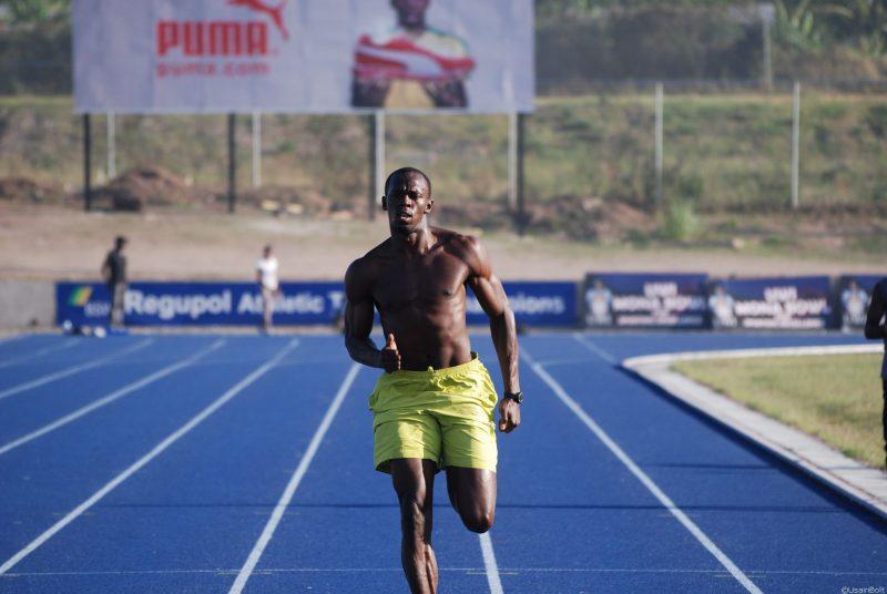 Usain Bolt cởi trần chạy trên đường đua.