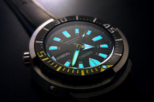 đồng hồ nam Seiko màu đen, chí tiết xanh và vàng.