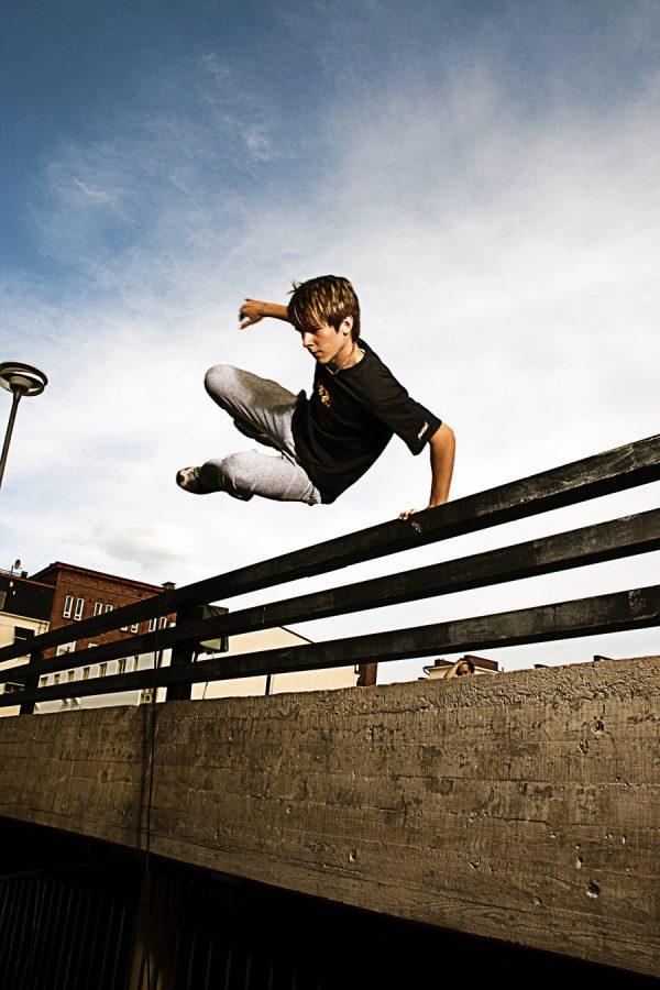 Parkour có phải là trò chơi mạo hiểm? chàng trai trẻ mặc áo đen nhảy qua hàng rào.