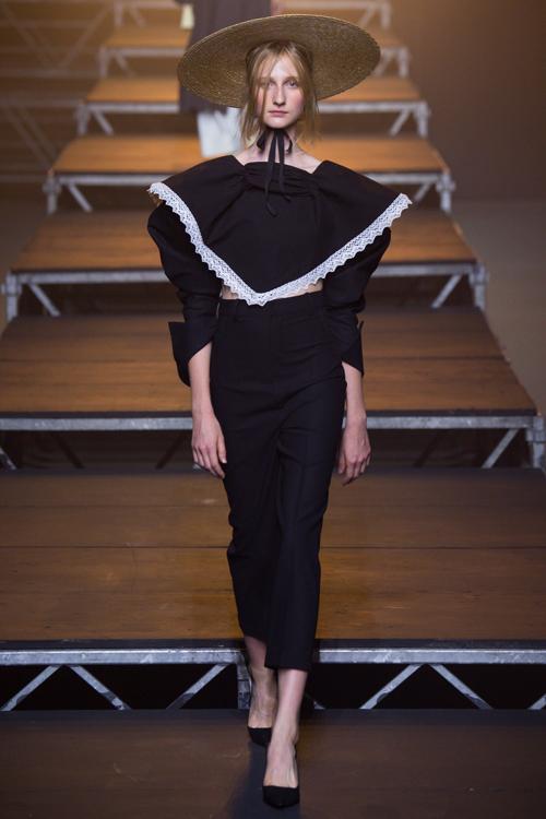 Simon Porte Jacquemus: người mẫu mặc áo crop top tay dài có yếm màu đen, quần tây ống cropped màu đen và đội mũ cói.