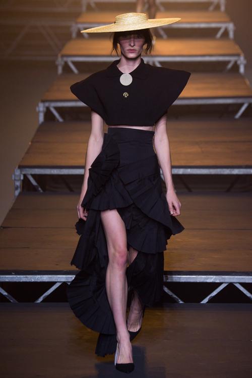 Simon Porte Jacquemus: người mẫu mặc áo crop top đen, chân váy xòe nhiều lớp màu đen  và mũ cói.