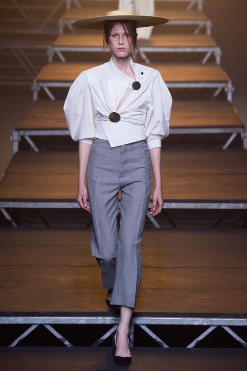 Simon Porte Jacquemus, người mẫu mặc áo trắng tay phồng, quần tây cropped màu xám và đội mũ.