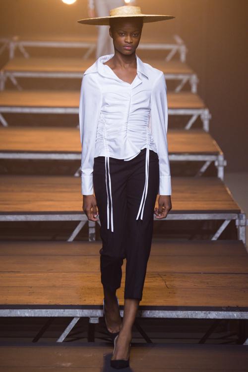 Simon Porte Jacquemus: người mẫu đội mũ, mặc áo sơ mi ôm màu trắng có 2 hàng dây cột và quần cropped màu đen.