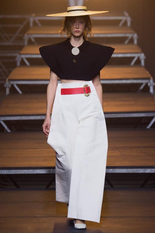 Simon Porte Jacquemus: người mẫu mặc áo crop top đen, quần trắng ống rộng.
