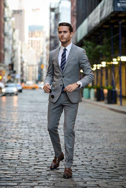 9 điều về suit nam cần lưu ý: người đàn ông mặc suit xám, tay cầm kính mát.