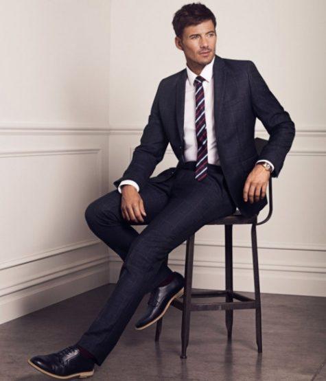 9 điều về suit nam cần lưu ý: người mặc suit xanh navy, ngồi trên ghế.