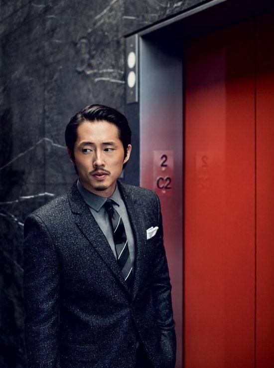 Steven Yeun trong bộ suit xám của Givenchy, đứng trước của thang máy màu đỏ.