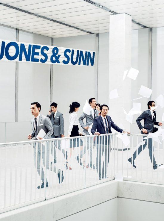 Steven Yeun trong bộ suit của John Varvatos, đứng tại hành lang.