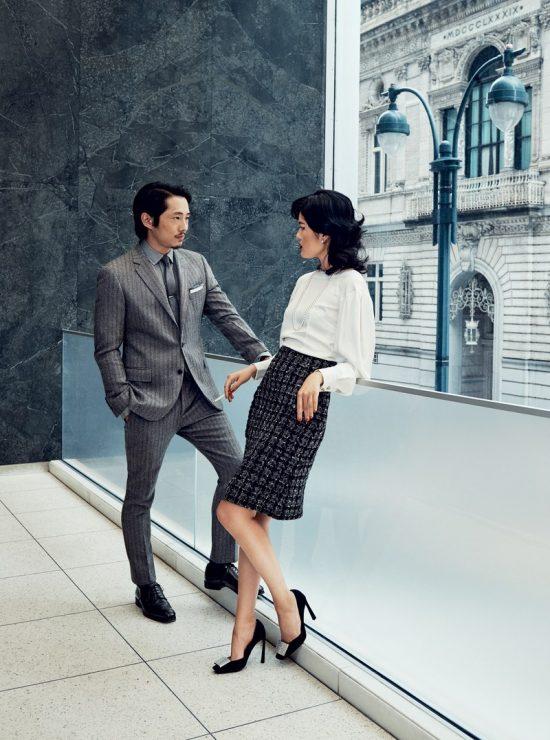 Steven Yeun mặc suit xám sọc của Todd Snyder, đứng trò chuyện cùng cô gái.