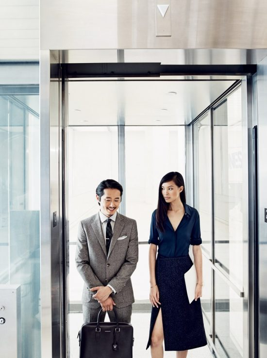 Steven Yeun trong bộ tweed suit xám nhạt, đứng cùng cô gái áo xanh - váy xám xẻ tà.