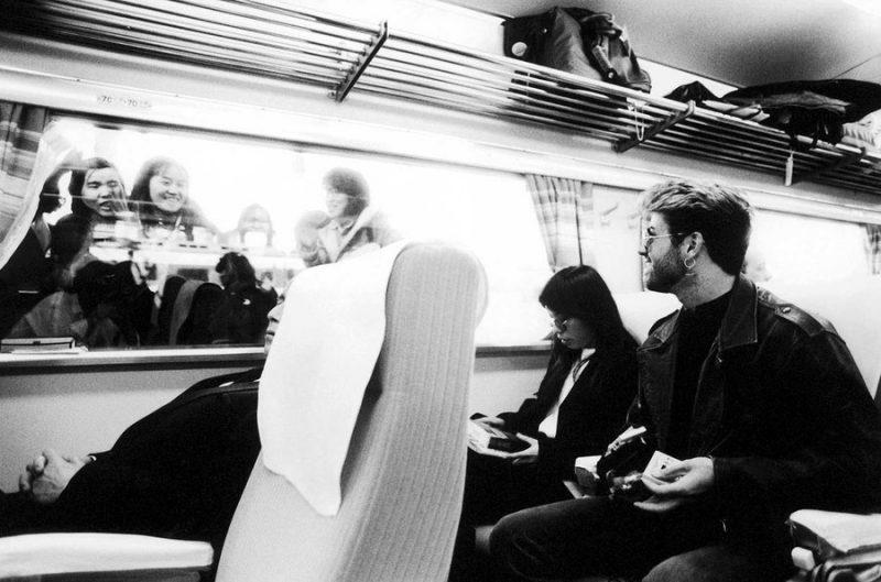 George Michael cùng bạn gái Kahty Yeung trong một toa xe tàu hỏa và người hâm mộ trong tour lưu diễn tại Nhật vào tháng Ba, 1988.
