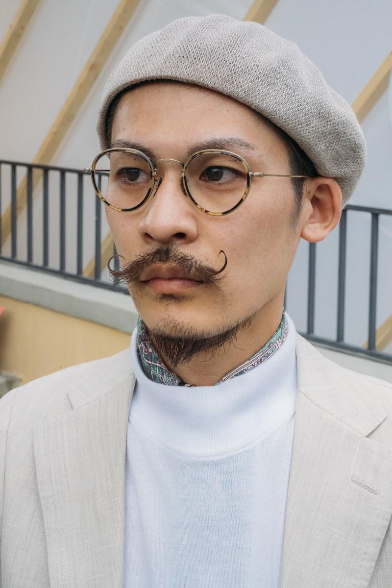 Chiếc mũ beret xám và chiếc kính tròn gọng mảnh càng tăng thêm vẻ nghệ sỹ cho chàng trai vớ bộ ria ấn ượng