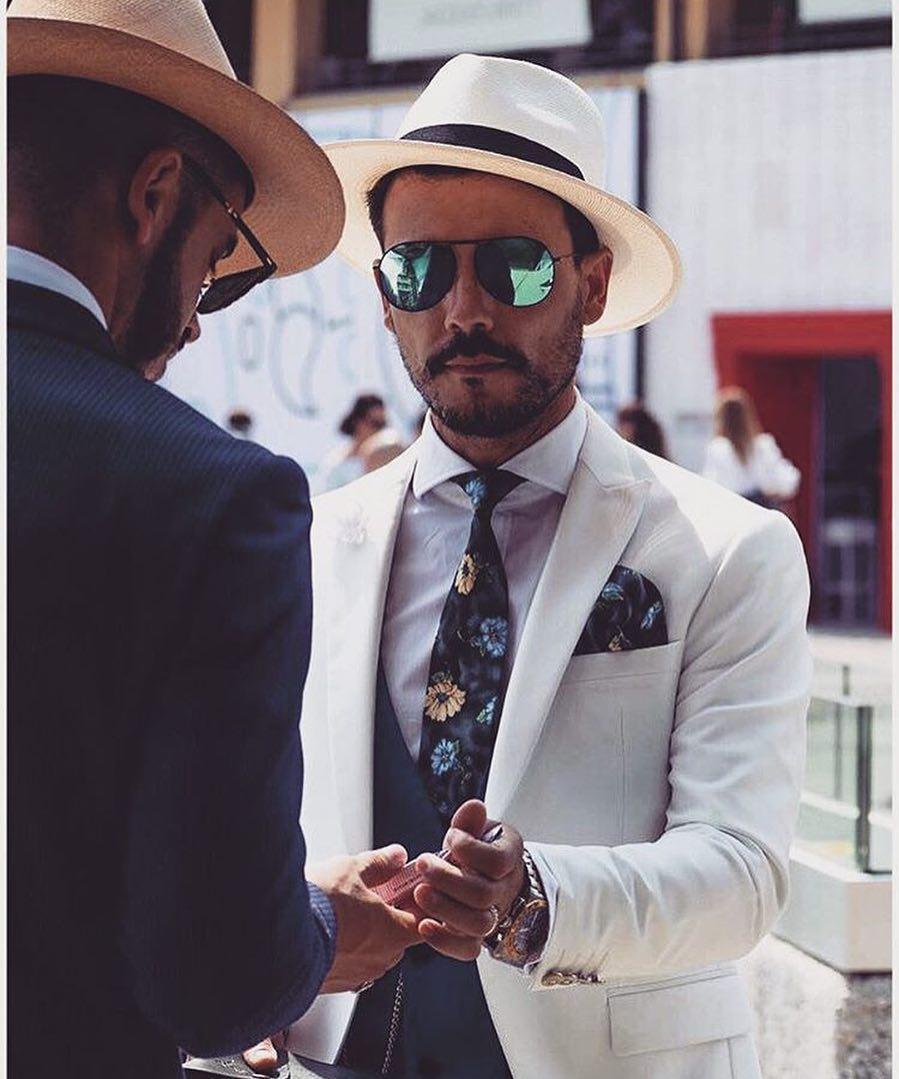 Mũ trắng ton sur ton với suit trắng càng khiến chiếc cà vạt hoa và chiếc kính tráng gương trở nên nổi bật