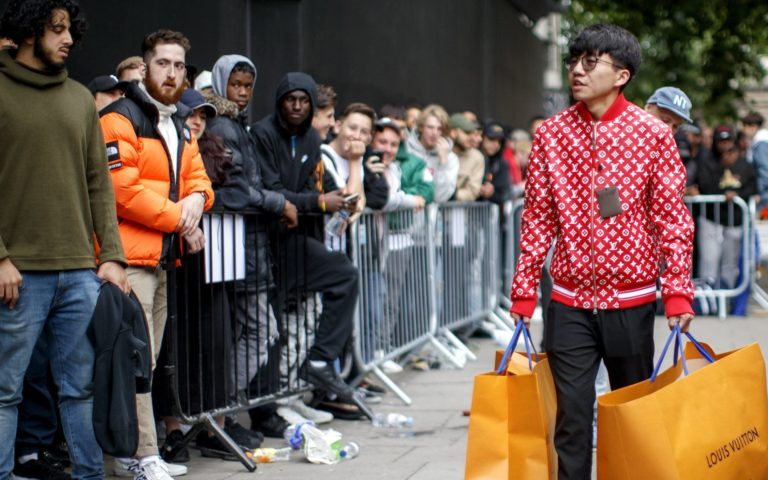 Jae Sung - A man walks away with his purchases as people queue for Louis Vuitton special edition sale on the Strand in central London on June 30, 2017. Picture credit: Tolga Akmen
