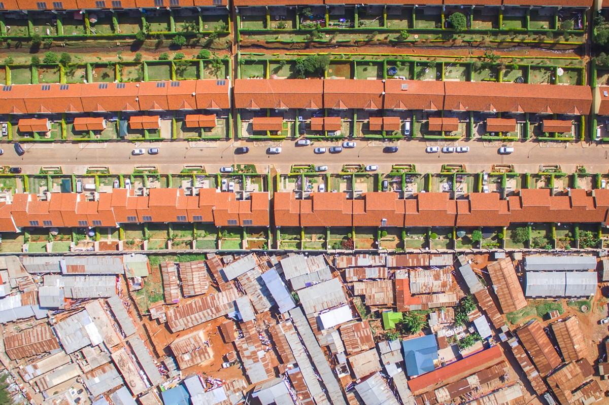 Bức ảnh được chụp tại Nairobi, thủ đô đồng thời là thành phố lớn nhất của Kenya. Chỉ với một bước từng mỏng như ở bên trên là sự giàu có thịnh vượng còn phần dưới là những ngôi nhà xập xệ. Ảnh: Johnny Miller