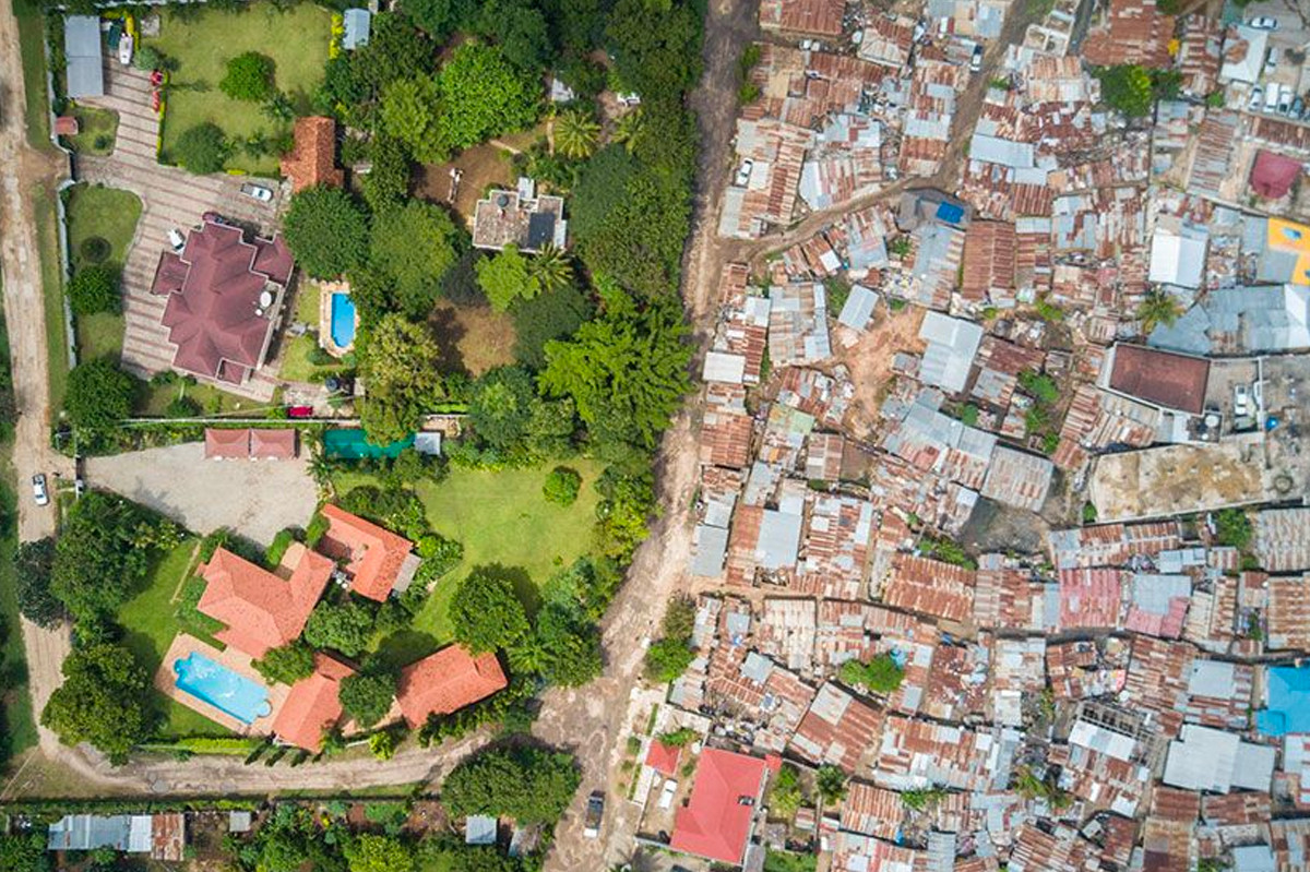 Bức ảnh chụp từ trên cao thể hiện sự đối lập giữa một bên là đầy rẫy những ngôi nhà mái tôn xập xệ và bên kia là những ngôi nhà cực kỳ vương giả ở Tanzania. Ảnh: Johnny Miller
