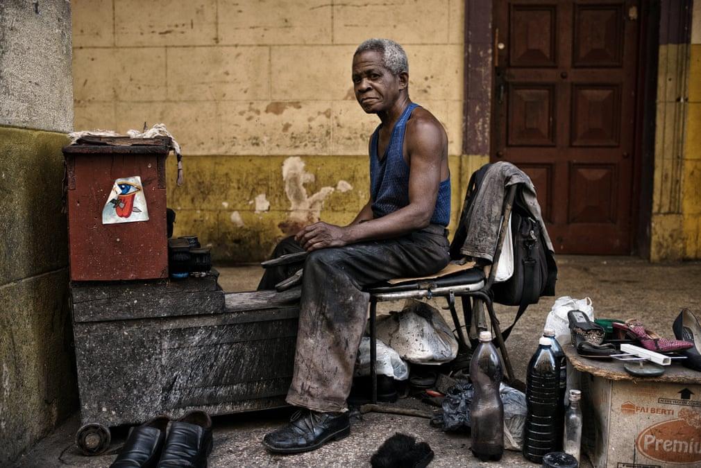 Bức ảnh ghi lại khoảnh khắc nghỉ ngơi hiếm hoi của một người thợ đánh giày ở Havana. Nhìn ông ta như đang tỏa ra ánh sáng kì diệu giữa một khoảng không trầm lặng. Ảnh: Simon Morris