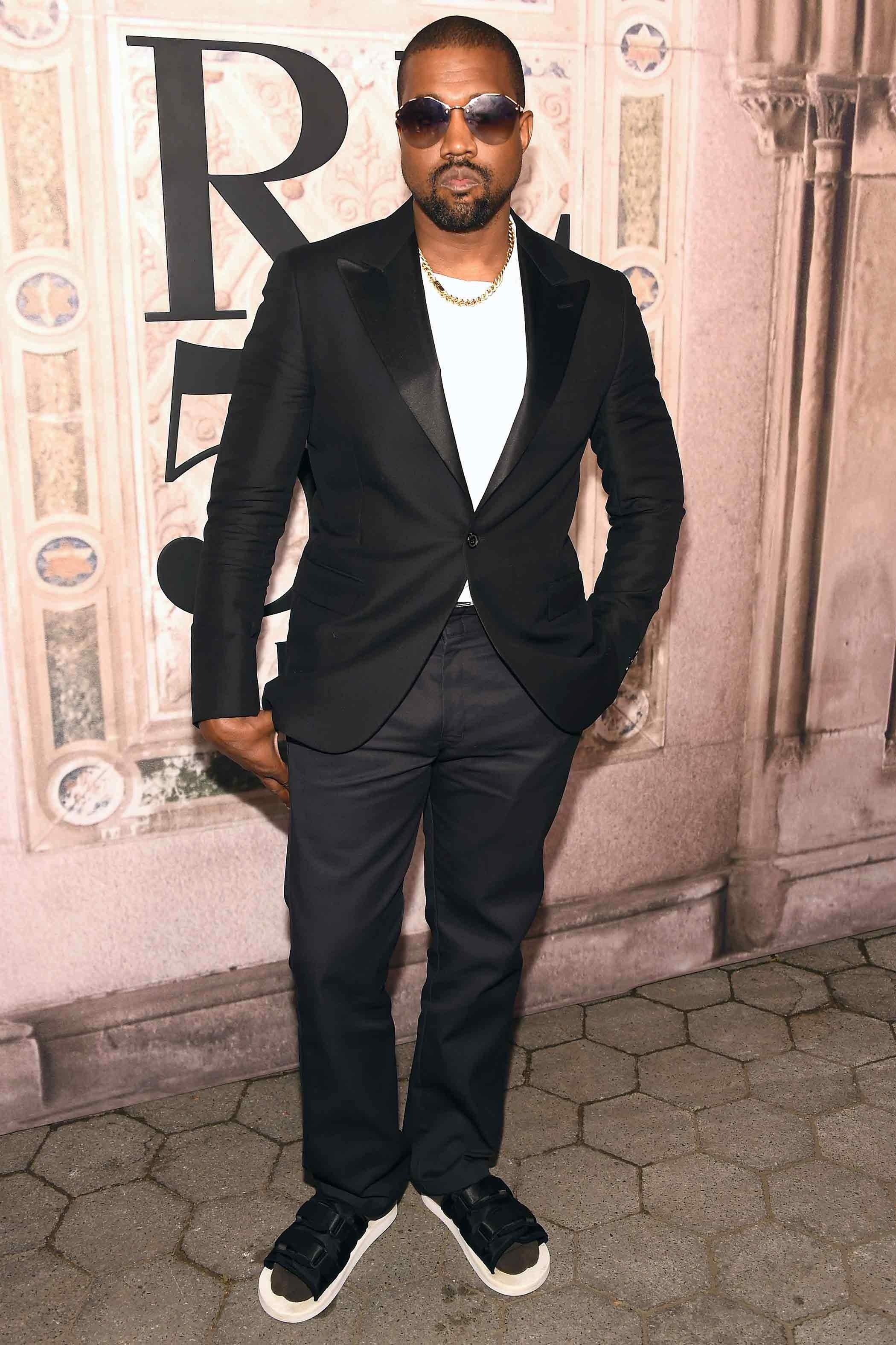 Kanye West gay ấn tượng khi phối bộ suit đen kinh điển cùng đôi dép lê đơn giản. Ảnh: GQ