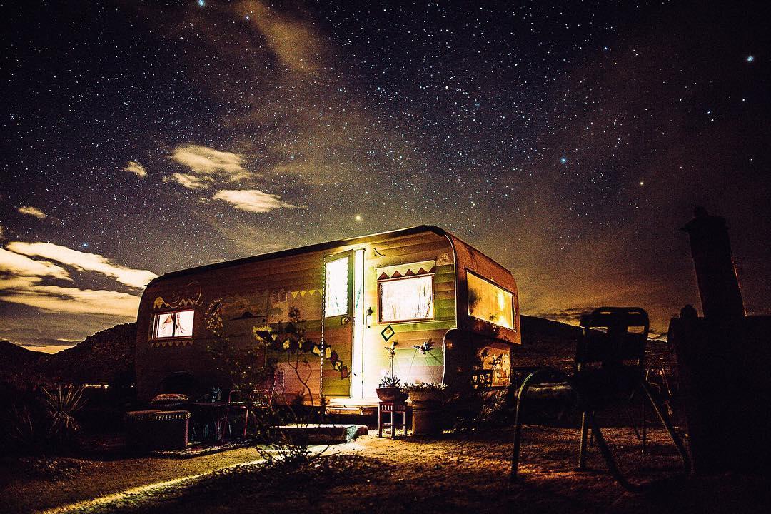 Bức ảnh du lịch ấn tượng được chụp tại công viên quốc gia Joshua Tree về một ngôi nhà xe buýt rực rỡ ánh sáng. Ảnh: André Josselin
