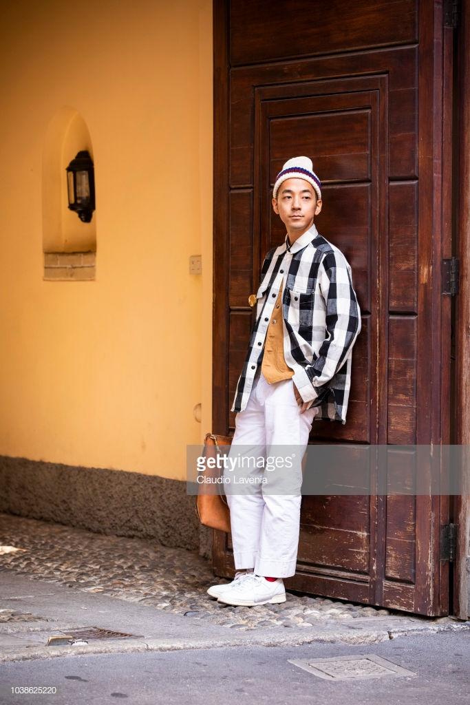 Sơ mi kẻ sọc bản to layer với áo phông cam tinh và mũ len tinh nghịch. Ảnh: Getty Images