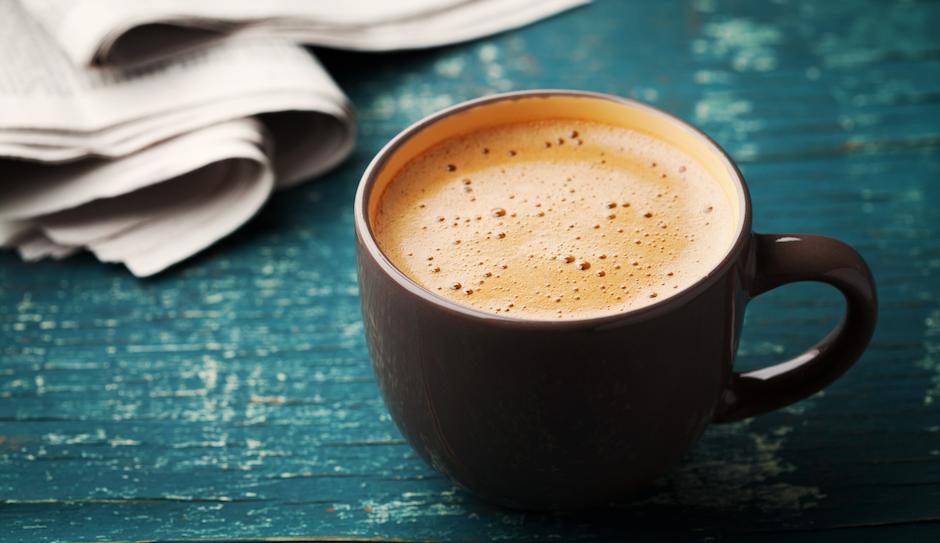Coffee mug with newspaper on teal rustic table, cozy breakfast, vintage style