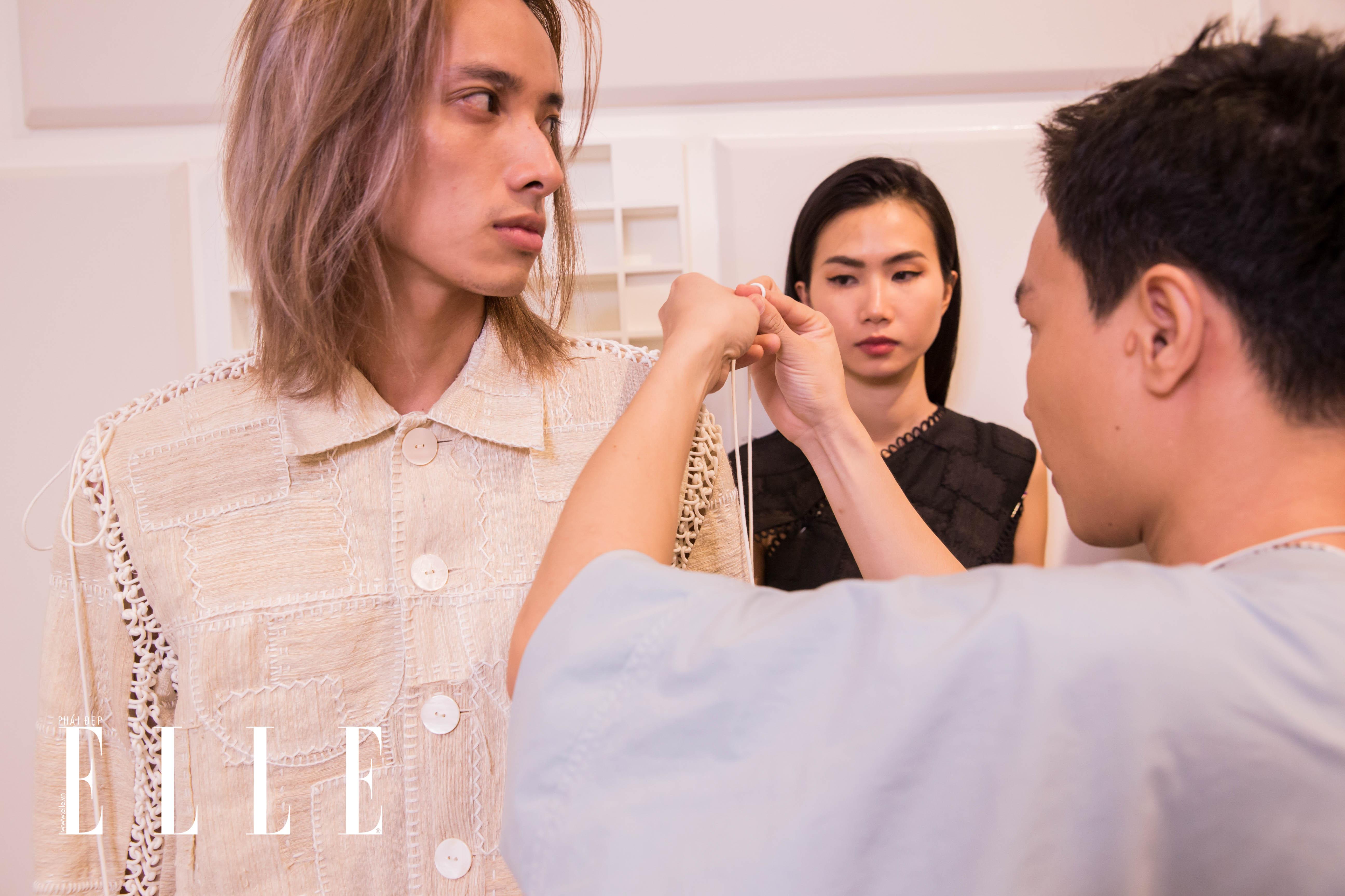 Nhà thiết kế Nguyễn Hoàng Tú chỉnh trang lại y phục cho người mẫu Việt Dũng. Ảnh: ELLE Việt Nam