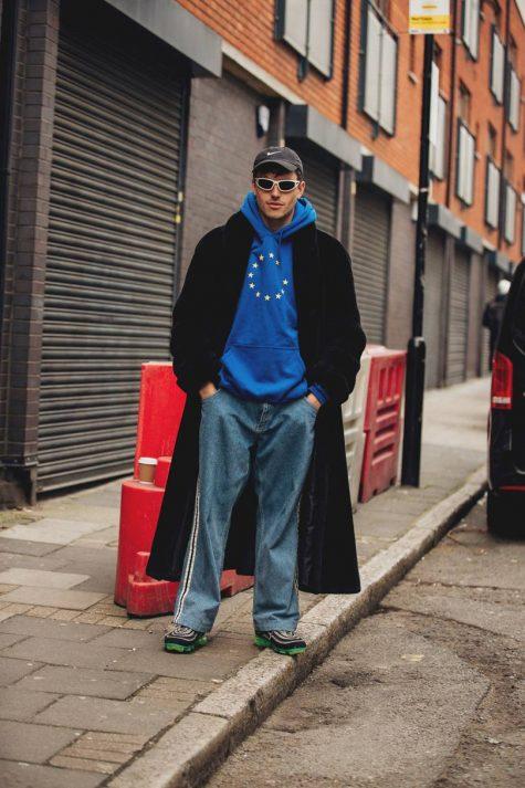 Quần denim oversized đi với hoodie và áo khoác trench coat đen đi cùng sneaker, kính viền trắng mạnh mẽ, hiện đại. Ảnh: Vogue UK