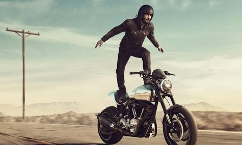 diễn viên Keanu Reeves đứng bên trên chiếc xe mô tô phân khối lớn