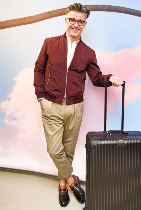 diễn viên eric rutherford mặc áo khoác bomber nâu đỏ