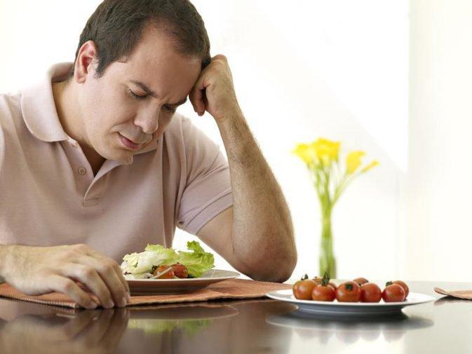 hình ảnh một người đàn ông mặc áo polo có triệu chứng chán ăn trước dĩa salad