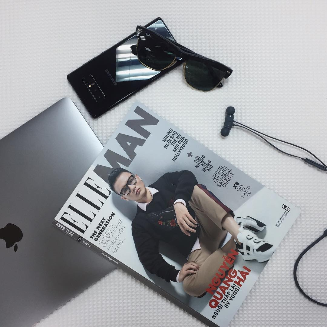 hình flat lay báo ELLE Man Quang Hải và Macbook và điện thoại samsung