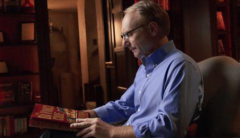 nhà văn Dan Brown cầm quyển Mật mã Da Vinci