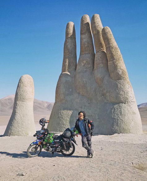 Trần Đặng Đăng Khoa tại bức tượng Mano Del Desierto (Bàn tay của sa mạc) trong sa mạc Atacama, Chile
