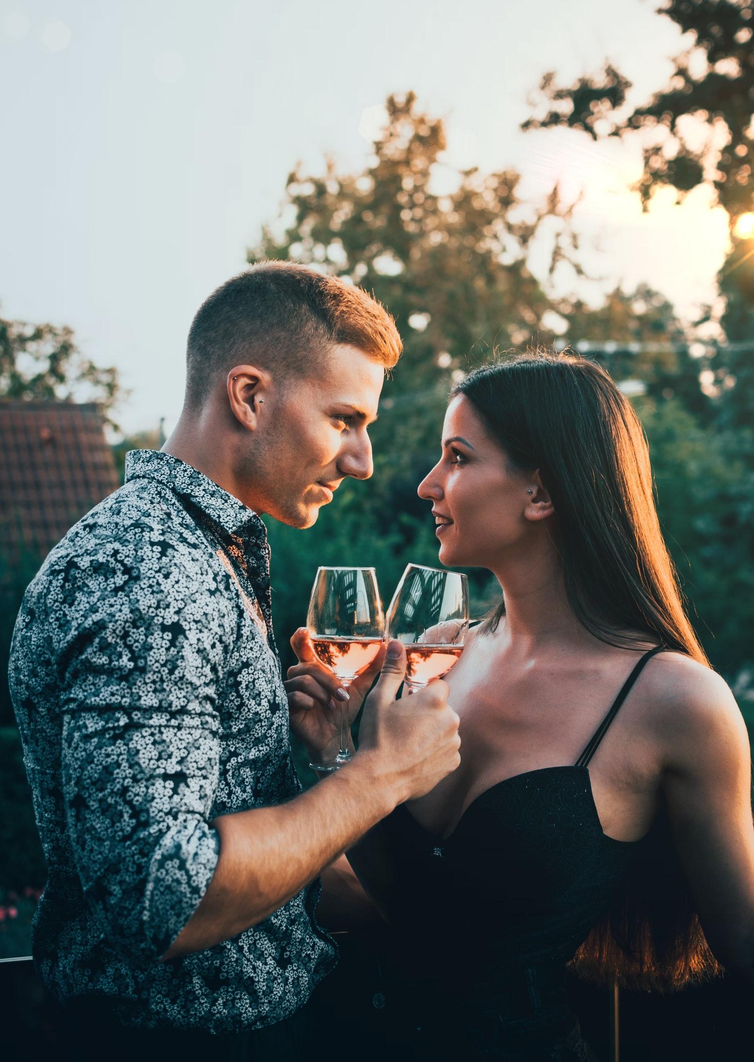 tính cách đàn ông sư tử khi yêu - chàng trai và cô gái cầm ly rượu nhìn vào mắt nhau