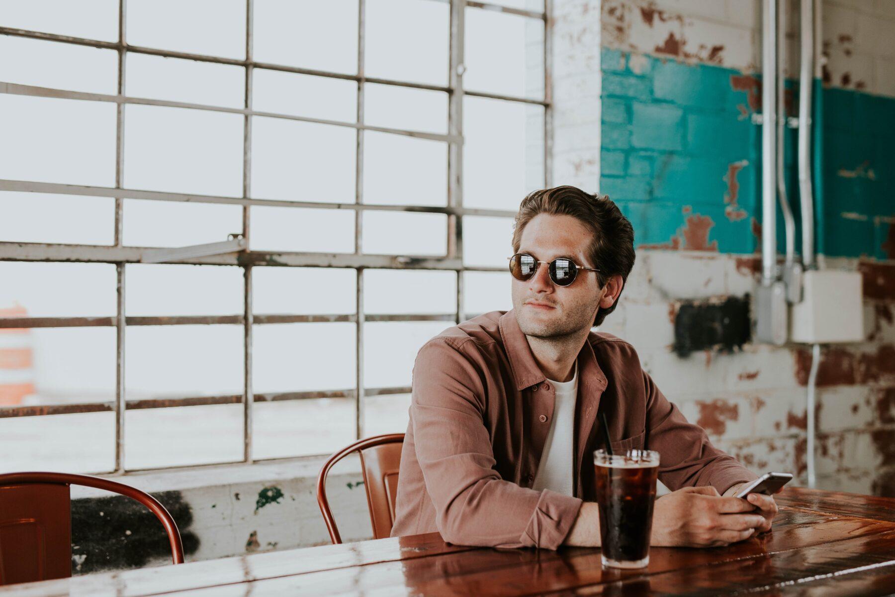 đàn ông xử nữ khi yêu - chàng trai cầm điện thoại trong quán cà phê