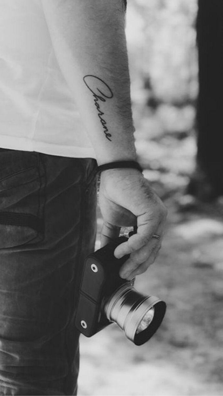 người đàn ông với hình xăm tên cùng chiếc máy ảnh- hình xăm nam giới - 2019 - elle man