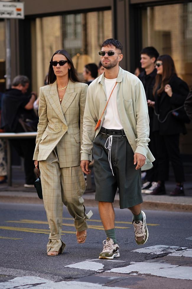 áo sơ mi tông xám trung tính khoác ngoài kết hợp cùng quần short kaki cùng tông sẫm và giày sneaker đi kèm luôn tạo nên sự năng động cho người mặc