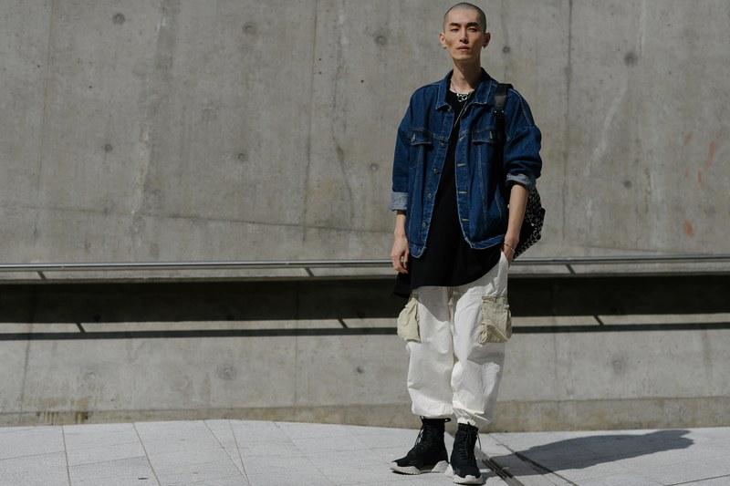 Lối ăn mặc theo phong cách khá là Normcore với áo thun oversize đen bên trong, khoác ngoài chiếc áo jean bụi bặm và quần kaki oversize túi hộp cá tính, đi kèm với đôi giày sneaker cổ cao đã tạo nên một tổng thể hài hoà về mọi thứ