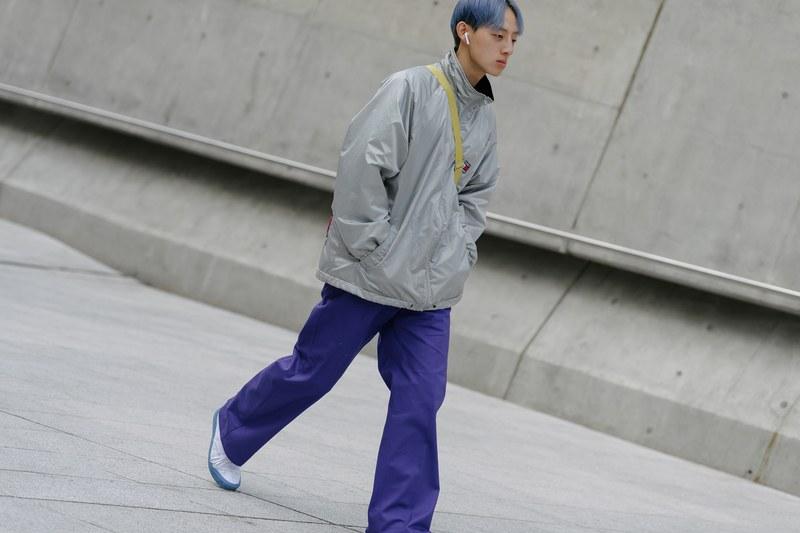 Nhấn nhá bằng màu sắc là một cách khá hay ho để tạo được điểm nhấn cho trang phục nhưng vẫn không quá phô trương. Giống với chàng trai này mặc trên người một chiếc quần ống rộng màu tím nổi bật cùng tông màu tóc, đi kèm với áo khoác vải dù và một đôi giày sneaker cơ bản