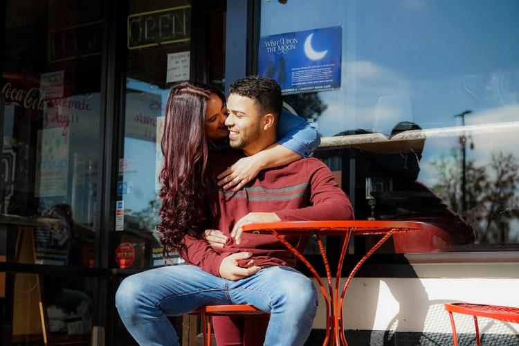 cặp đôi đang ôm nhau trước cửa hàng