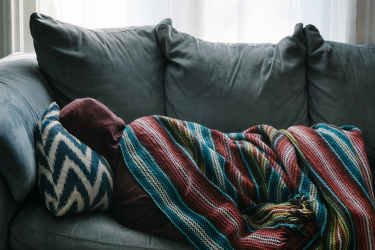 người bị ốm nằm trên sofa.