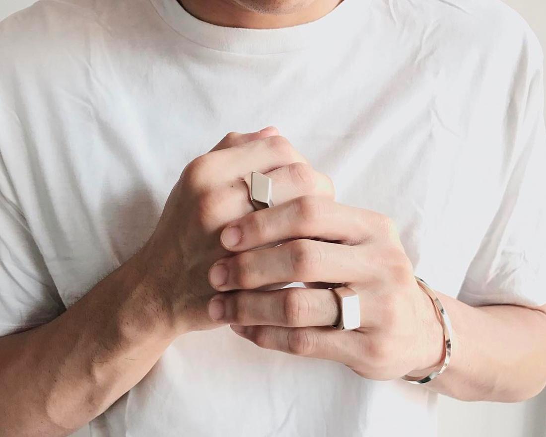 tay đeo vòng tay và nhẫn bạc.
