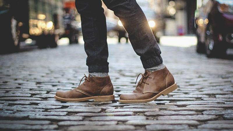 người đàn ông đang đi giày chukka ngoài phố