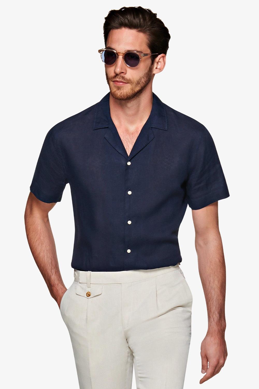 Người mẫu mặc áo sơ mi ngắn tay màu xanh navy và quần trắng ngà của suitsupply.