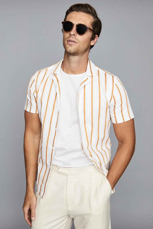 người mẫu mặc áo sơ mi sọc dọc phối cùng áo thun trắng và quần màu kem của Reiss.