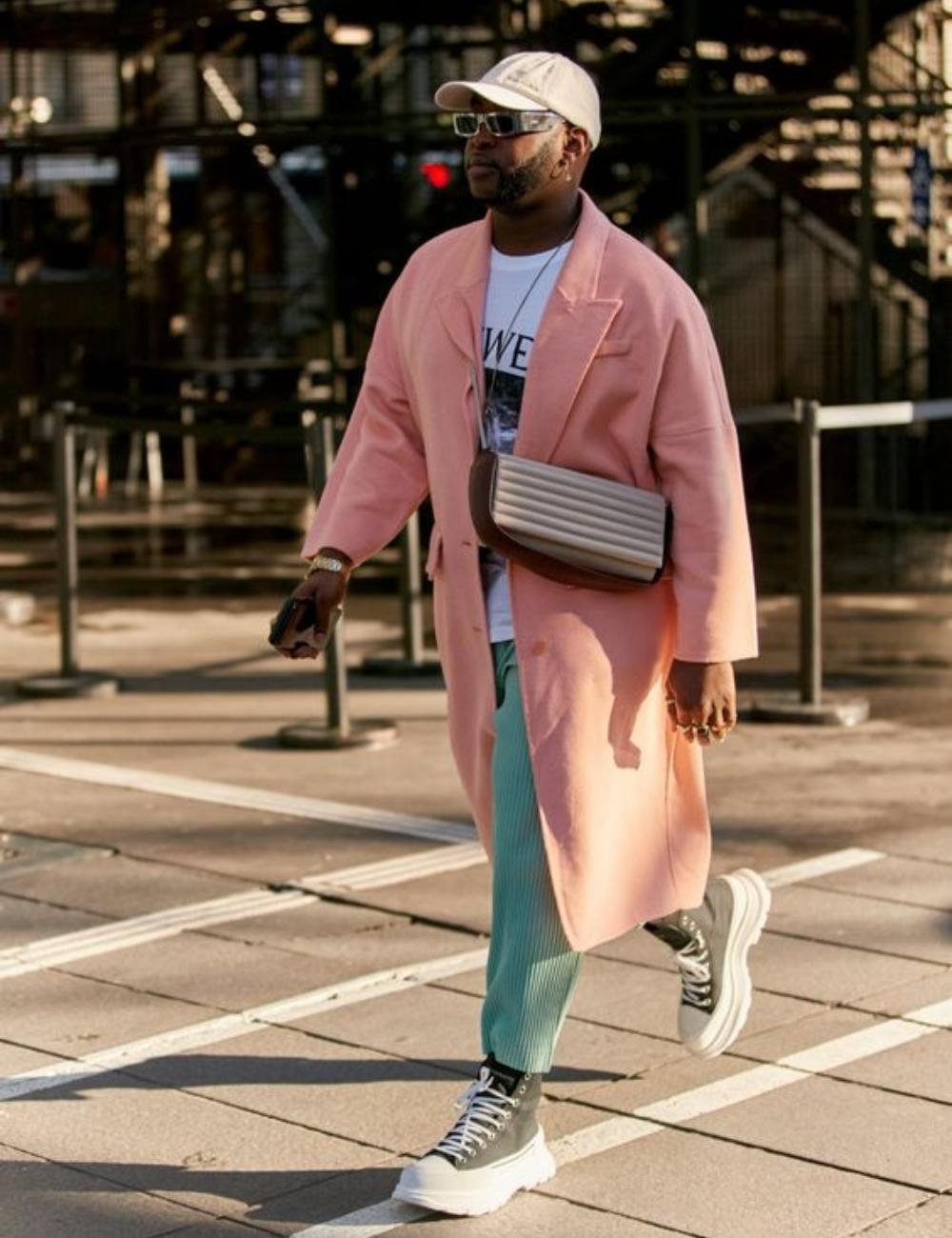 Người đàn ông mặc trang phục áo thun trắng, áo khoác và mũ lưỡi trai hồng, quần ply dập xanh lá và giày boots.