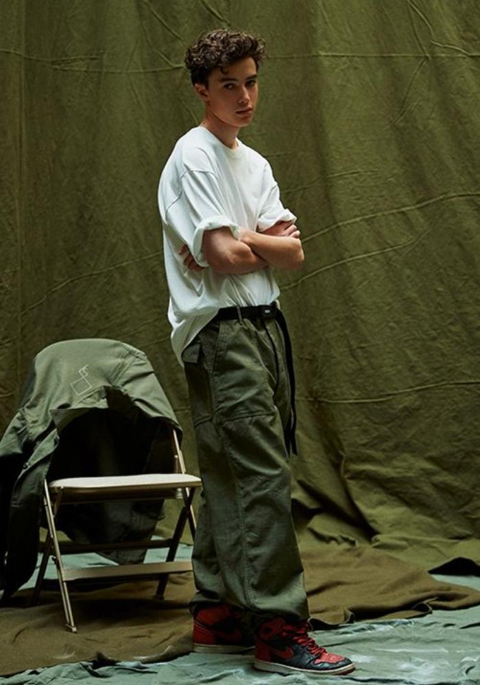 """chàng trai mặc outfit gồm áo sơ mi trắng và quần loose-fit xanh olive và một đôi Air Jordan """"Bred"""""""