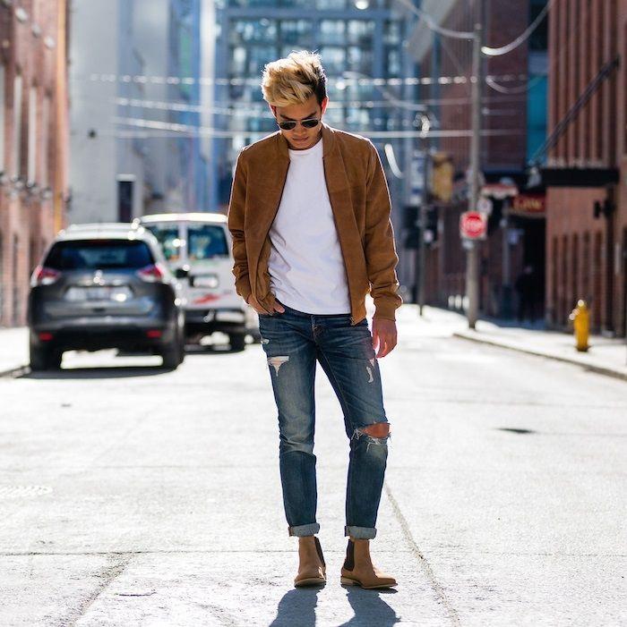 chàng trai mặc áo bomber nâu, áo thun trắng, quần jeans rách và giày chelsea boots nâu.